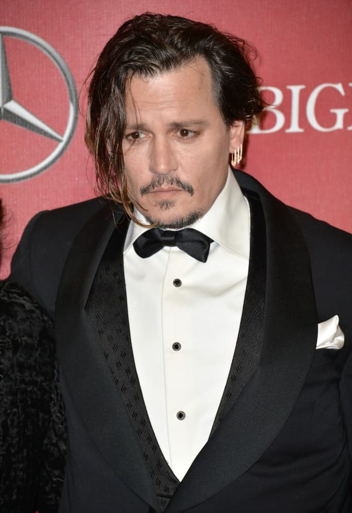 Last January 2, 2016, Actor Johnny Depp was at the 2016 Palm Springs International Film Festival Awards Gala. He wore a detailed black suit with bow that somehow compensates for his tousled and loose side-parted hair with highlights.