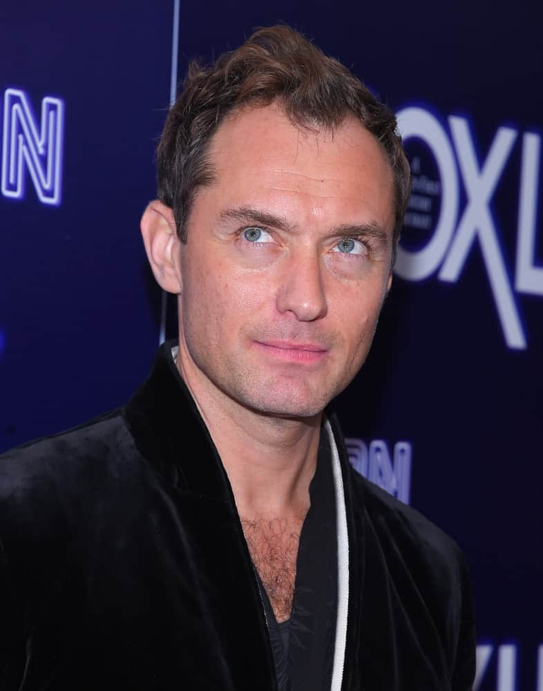 Jude Law's short curly hair was styled in a tossed up 'do with highlights when he arrived at the
