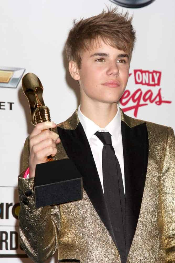 Justin Bieber appeared with a tousled, spiked 'do at the 2011 Billboard Music Awards at MGM Grand Garden Arena. Stunning and shimmering gold tuxedo completed the sleek look.