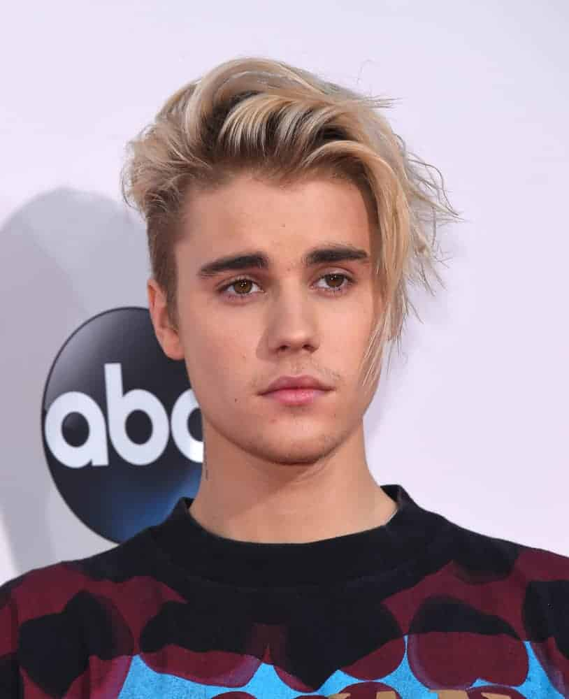 Justin Bieber dyed his hair golden blonde and styled a lengthy look when he appeared at the American Music Awards 2015 in Los Angeles, CA.