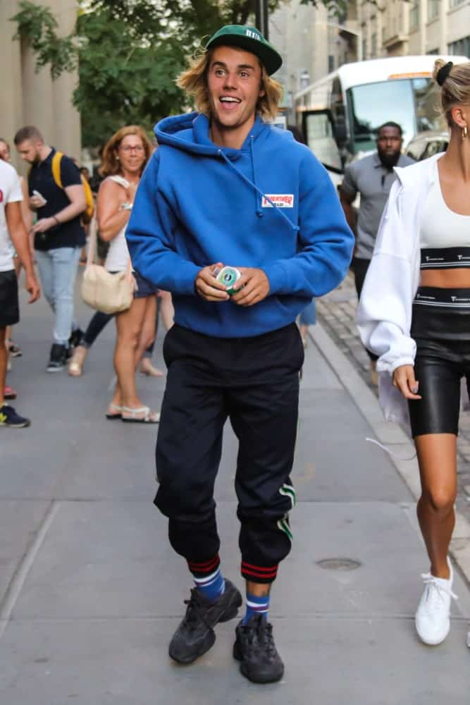Justin Bieber was spotted in New York City on July 12, 2018 wearing a green cap that complements his long blonde hair. The look was completed with a blue sweatshirt and black jogger pants.
