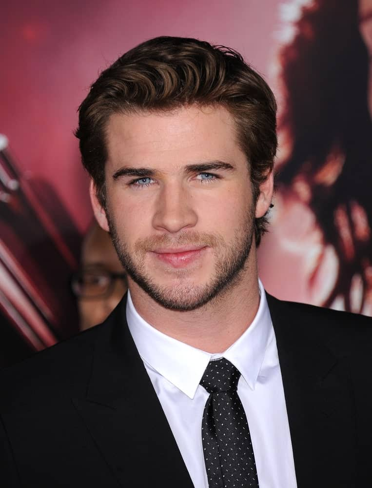 The actor is a head-turner in a black suit and pompadour hairstyle during the
