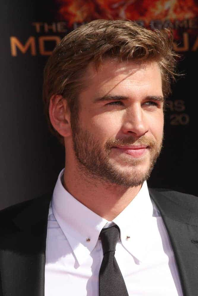 Liam Hemsworth had side-parted short hair with wavy locks at front during the Hunger Games Handprint and Footprint Ceremony at the TCL Chinese Theater, Los Angeles, CA in 2015.