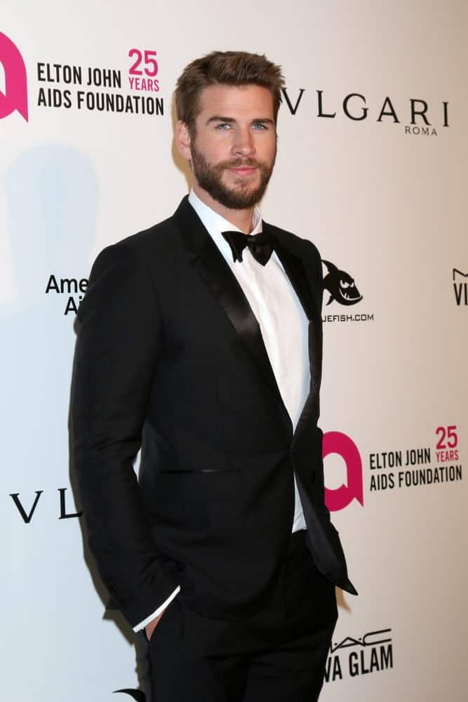 Liam Hemsworth was spotted at a 2018 Elton John AIDS Foundation Oscar Viewing Party last March 4, 2018 in a classic black suit and his short hair side-parted with some spikes in front.