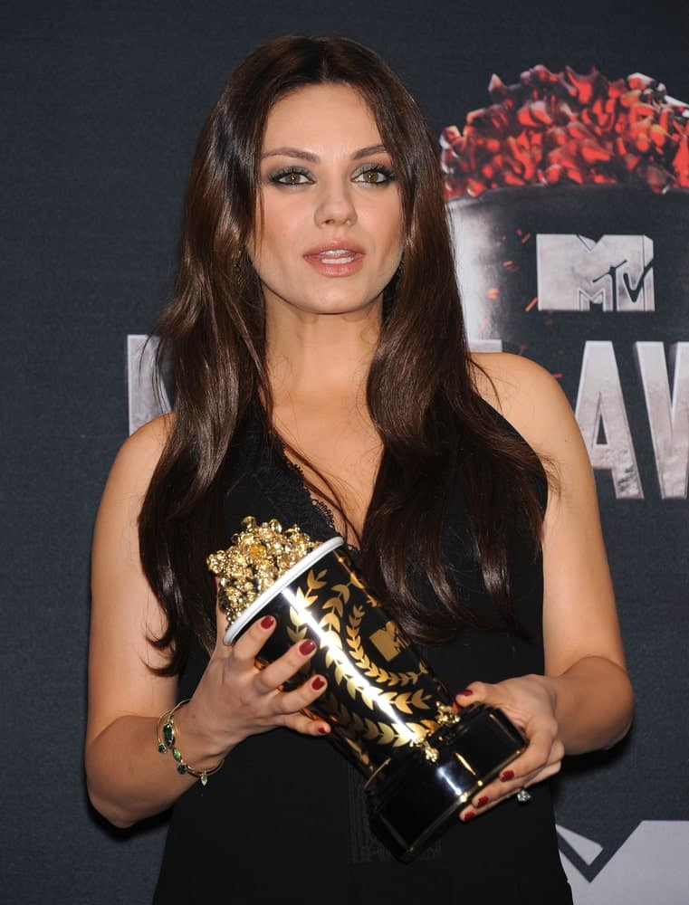 Mila Kunis was at the 2014 MTV Movie Awards - Press Room last April 13, 2014 in Los Angeles. She had a simple black dress to match her dark brown loose and tousled waves.