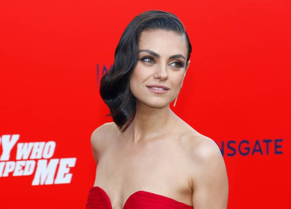 Mila Kunis was stunning and elegant in her sexy red dress complemented by a vintage look to her slick side-swept wavy hairstyle at the Los Angeles premiere of 'The Spy Who Dumped Me' held at the Regency Village Theater in Westwood last July 25, 2018.