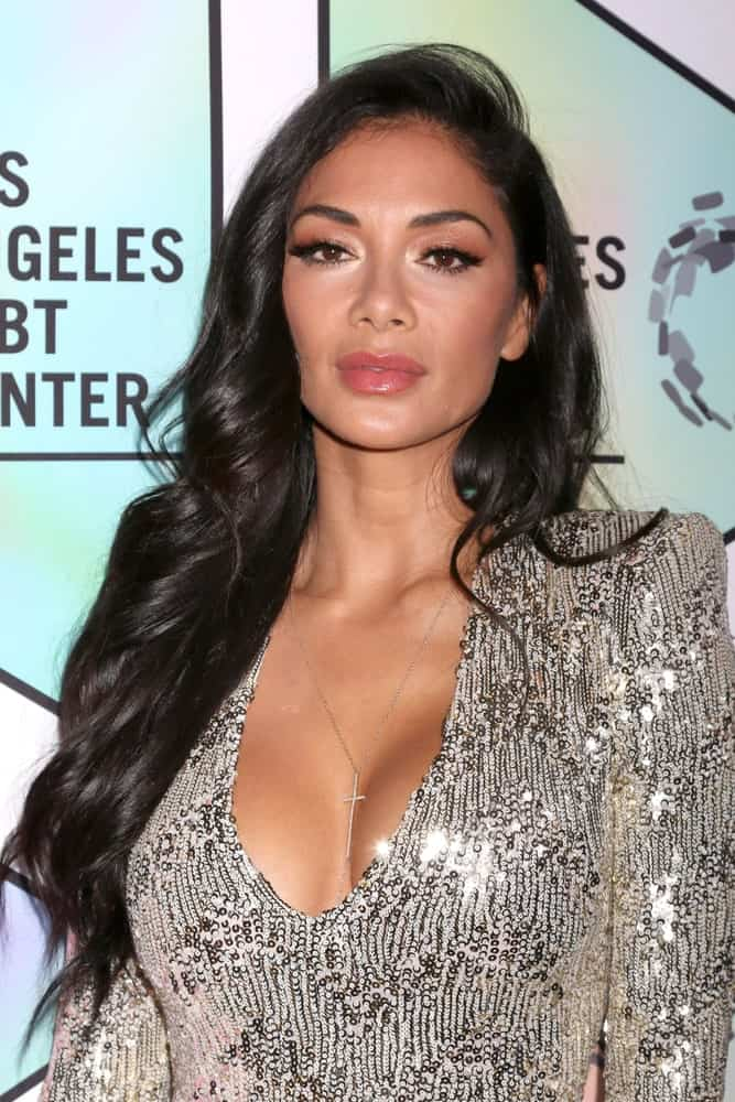 Looking all glamorous and seductive, Nicole Scherzinger shows off her loose wavy hair that's side-parted. She finishes the look with a stunning low V-neck dress which she wore during the LA LGBT Center`s 49th Anniversary Gala at the Beverly Hilton Hotel on September 22, 2018.