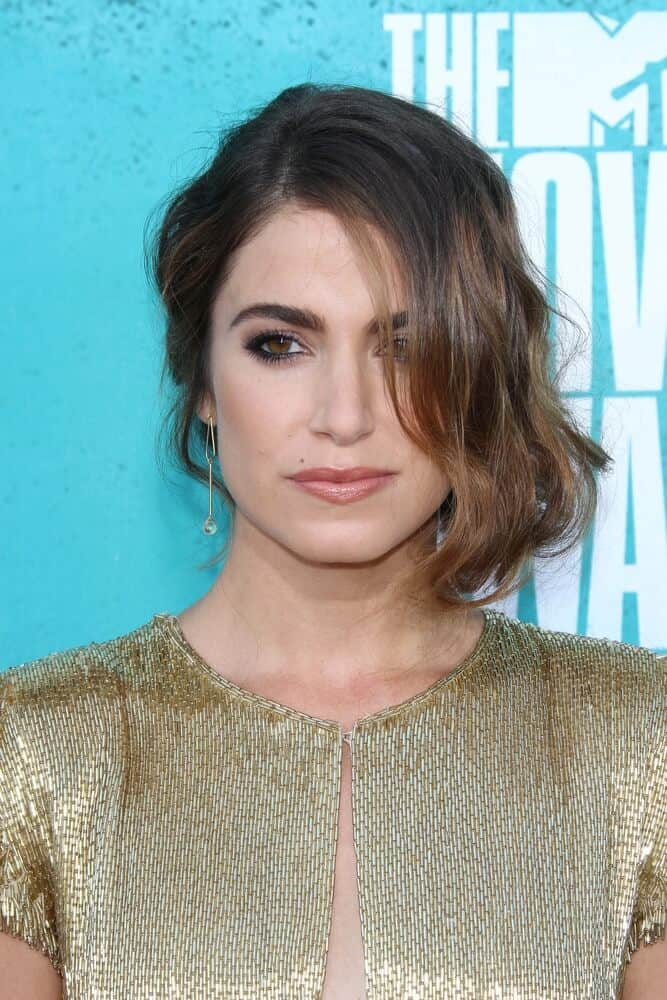 Nikki Reed once again surprised the crowd with her simple but elegant trademark look as she attended the 2012 MTV Movie Awards with a side-swept, wavy upstyle.