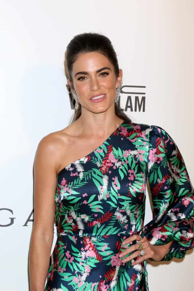Nikki Reed attended the 2018 Elton John AIDS Foundation Oscar Viewing Party on March 4th with her brunette hair on a low-tied ponytail. She paired it with silver earrings and a one-shoulder dress with foliage print.