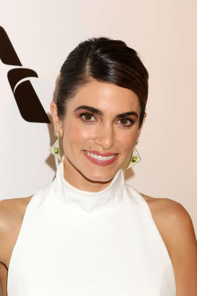 The actress exhibited a neat side-swept updo at the Elton John Oscar Viewing Party on the West Hollywood Park on February 24, 2019. She completed the look with a white halter dress and gorgeous triangular earrings.