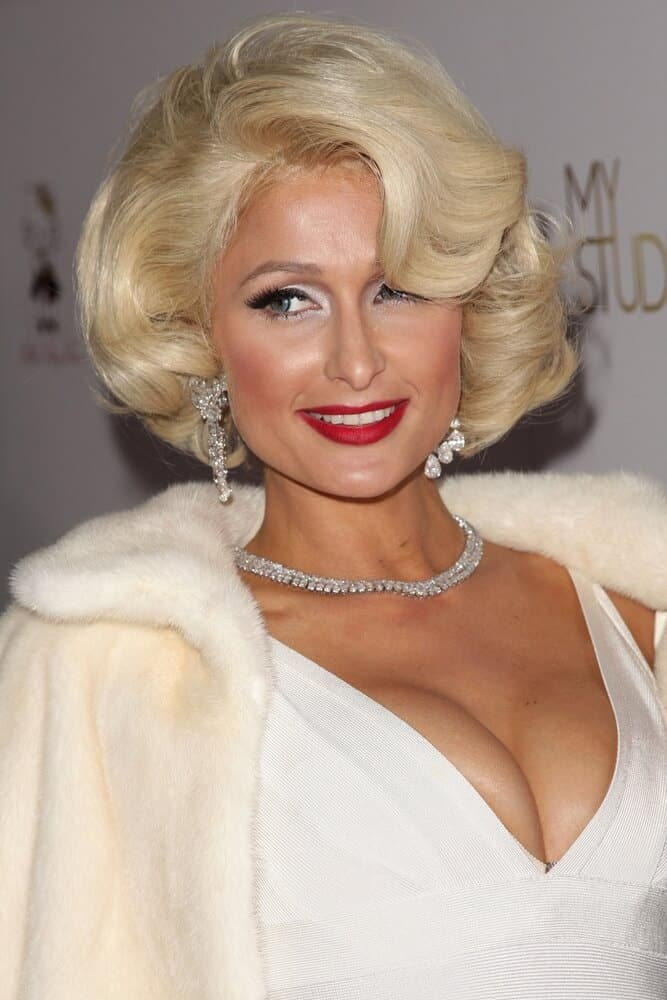 """Last August 10, 2010, Paris Hilton arrives at the Paris Hilton's """"Tease"""" Fragrance Launch in a classic vintage hairstyle and a bold red lipstick to match the look."""