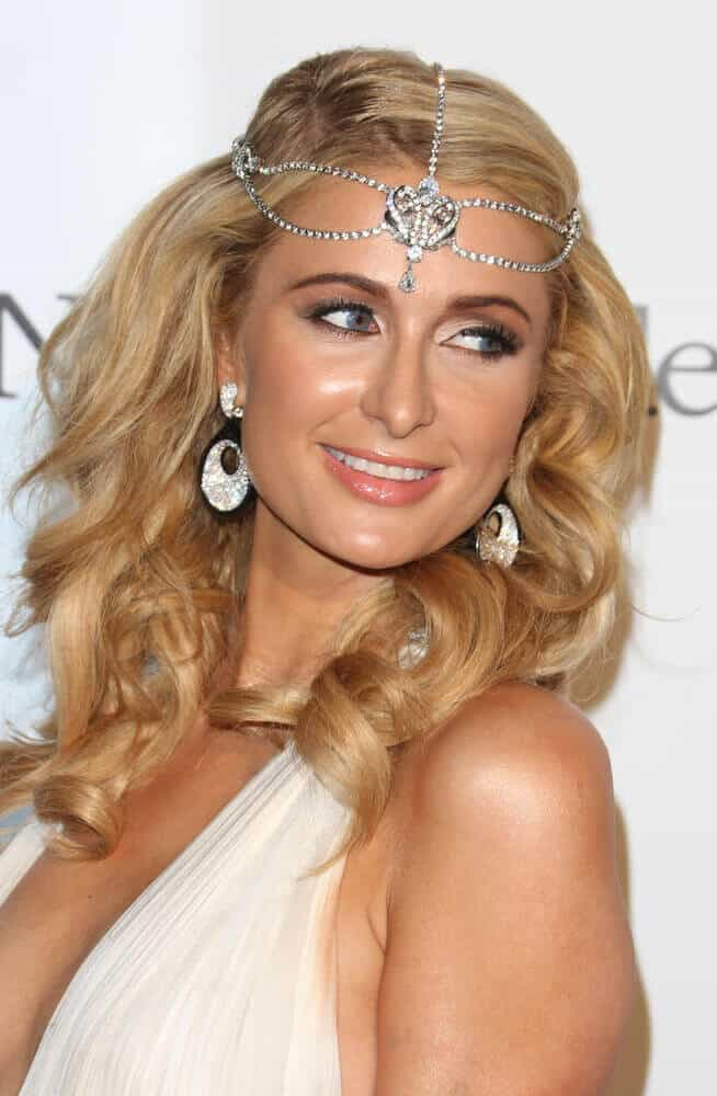 Paris Hilton at the 66th Cannes Film Festival - de Grisogono Party 2013, looking fresh and stylish with her curled hair decorated with some iconic embellishments.