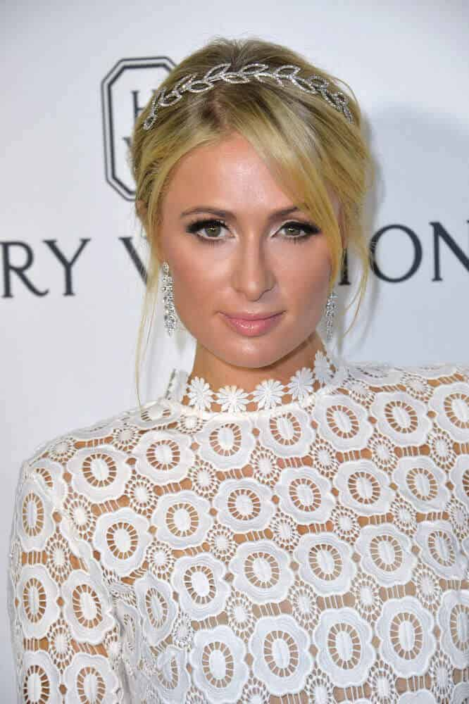 Paris Hilton is oozing with elegance in her simple upstyle enhanced with a decorative headband during the 2016 amfAR Inspiration Gala, October 27, 2016.