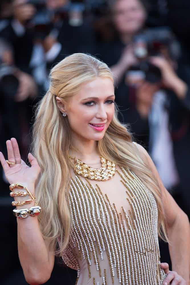 Paris Hilton waved hi at the 'Inside Out' premiere during the 68th annual Cannes Film Festival on May 21, 2015. She looked stunning in a sequined nude dress that matches her highlighted blonde locks styled in half updo.