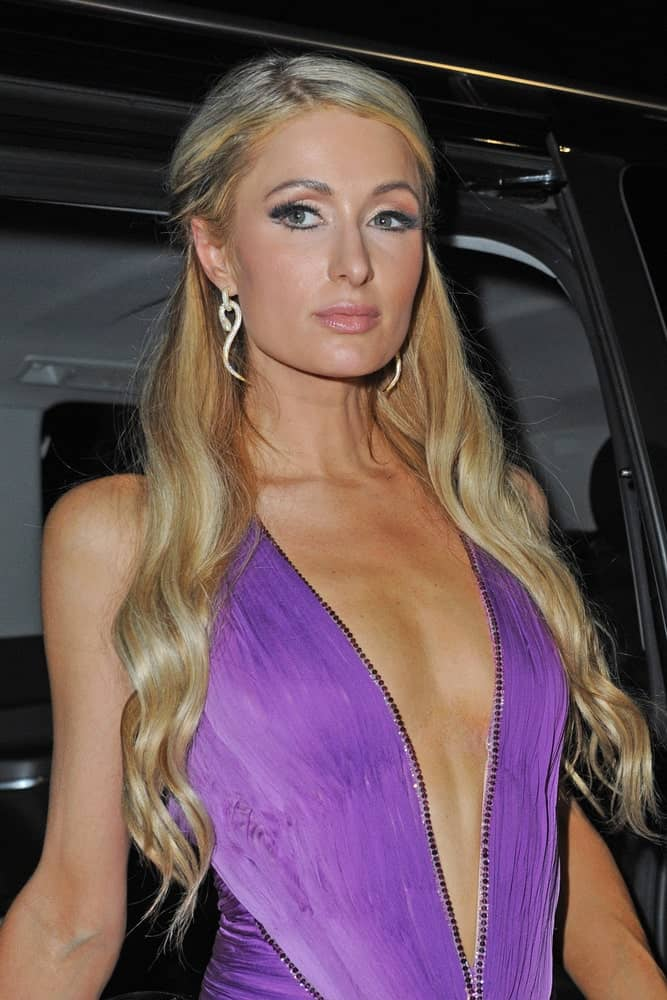The singer arrived at Just Cavalli disco - Paris Hilton for skincare on October 22, 2018 in a purple deep V-neck dress and her highlighted blonde waves styled in half updo showing off her eccentric earrings.