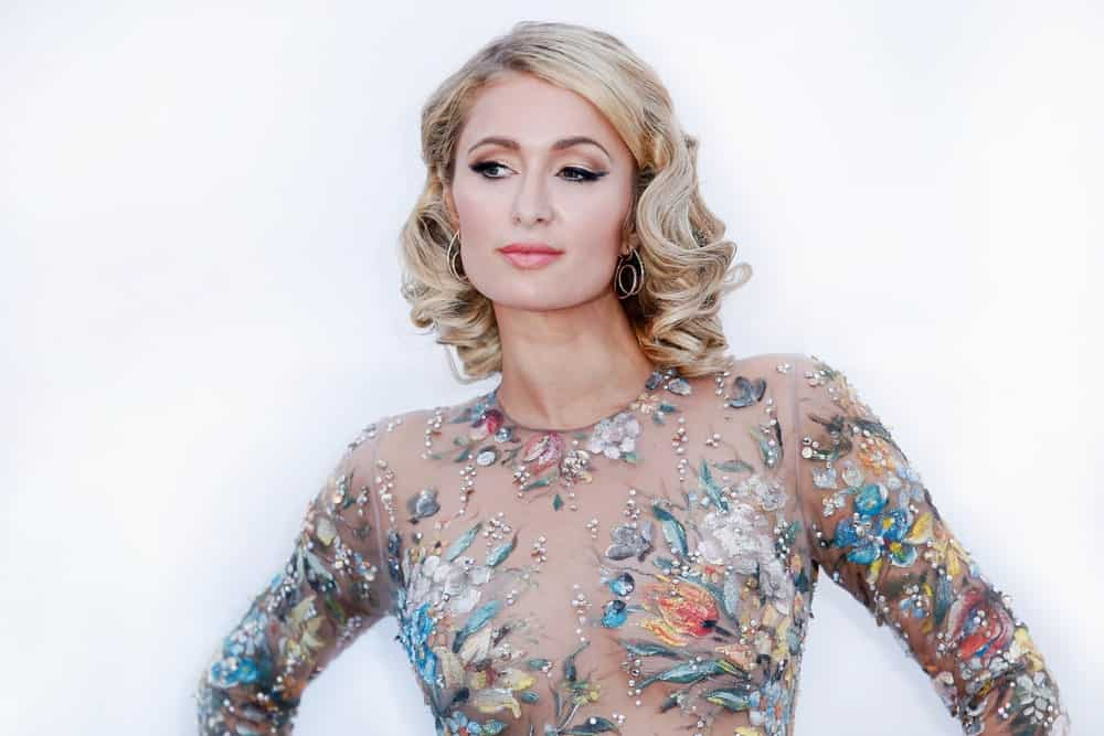 Paris Hilton looked stunning in a floral see through dress that she wore during the amfAR Gala Cannes 2018 at Hotel du Cap-Eden-Roc on May 17, 2018. She paired it with her short blonde tresses beautifully curled and side-parted.