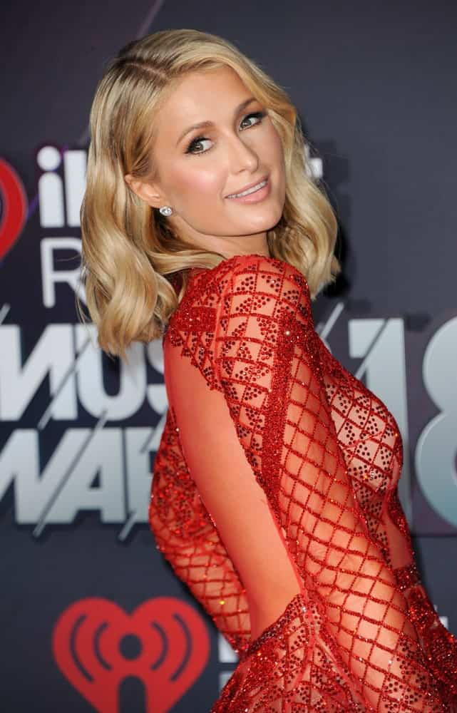 On March 11, 2018, Paris Hilton attended the 2018 iHeartRadio Music Awards held at the Forum in Inglewood, USA in a gorgeous red dress and her short blonde waves side-parted.