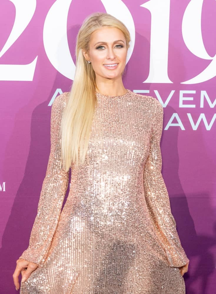 Paris Hilton looking charming and sweet with her loose blonde tresses pinned back on both sides. She paired it with a blush sequined dress during the 2019 FN Achievement Awards on December 3, 2019.