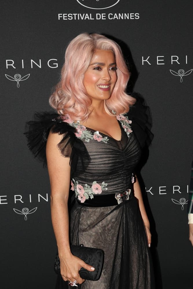 Salma Hayek attended the Women in Motion Awards Dinner for at the 70th Festival de Cannes last May 21, 2017 with a black purse that matches her black sheer dress that has pink flowers matching with her dyed wavy shoulder-length hair.