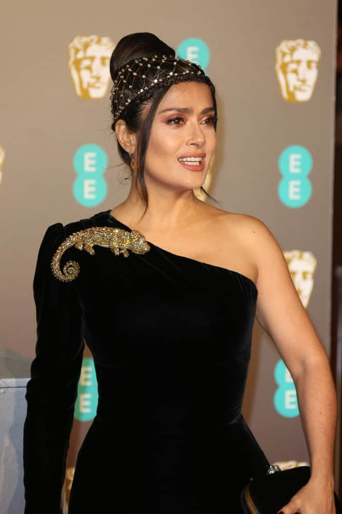 Last February 10, 2019, Salma Hayek attended the 72nd British Academy Film Awards at the Royal Albert Hall with a black asymmetrical dress to match her upstyle that has a top knot, crown braid and tendrils.