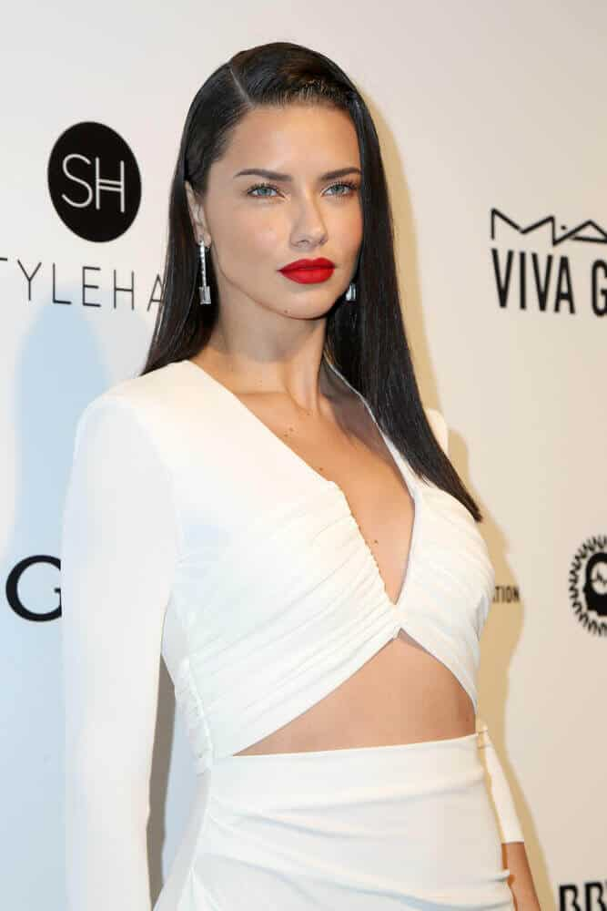 "Adriana Lima overflowed with elegance as she combined three simple styles together in one: a sleek and straight hairstyle, a ""bold lipstick, no eye shadow"" make-up look and a simple plain white dress. This gorgeous style was worn last February 26, 2017 at the 25th Annual Elton John Academy Awards Viewing Party."
