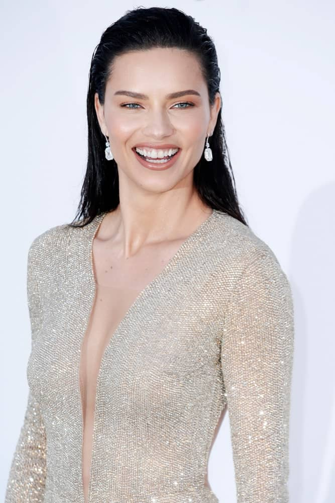 Adriana Lima arrived at the amfAR Gala Cannes 2018 at Hotel du Cap-Eden-Roc on May 17, 2018 in Cap d'Antibes, France. Her hairstyle was an elegant wet-look style that is brushed up to emphasize her gorgeous face.