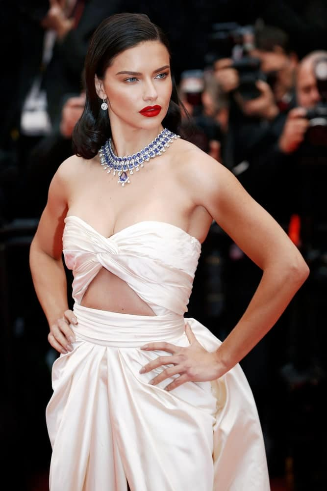 Adriana Lima was wearing a stunning white dress that is complemented with a classic dark pin curl side parted hairstyle at the screening of 'Burning' during the 71st Cannes Film Festival on May 16, 2018 in Cannes, France.