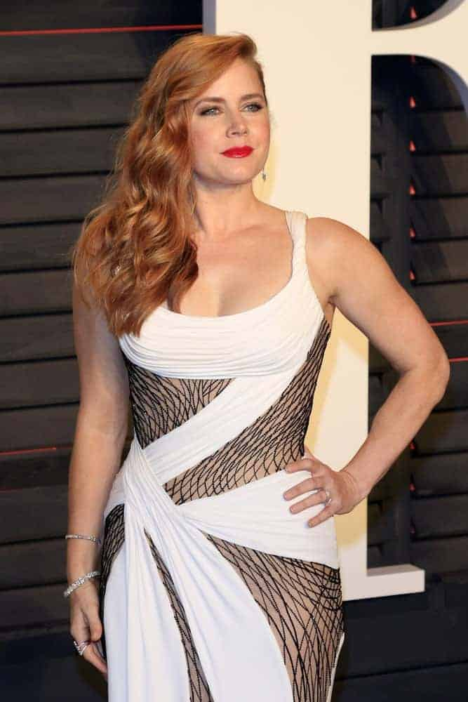 Amy Adams was at the 2016 Vanity Fair Oscar Party on February 28, 2016, in Beverly Hills, California. She paired her elegant dress with a long and wavy red hair that is side-swept and layered.