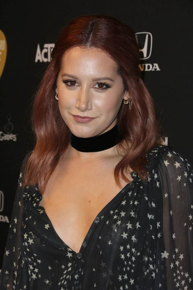 Tisdale upgraded her look during  the 2015 Guitar Hero Live Launch Party by going Mahogany. Her medium-length, reddish brown hair is arranged in a half-up style.