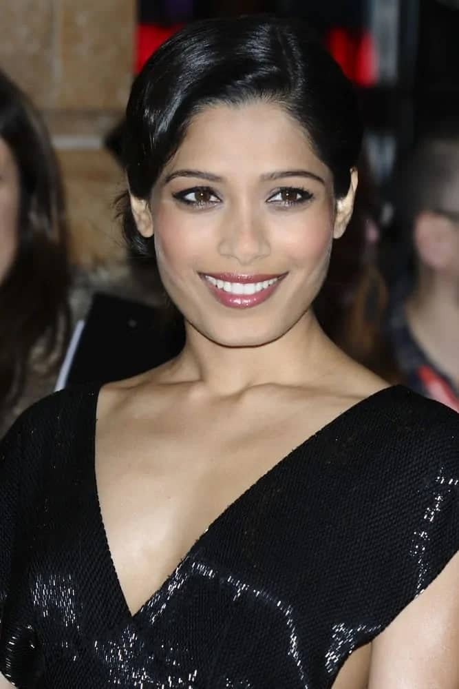 The lovely actress Freida Pinto showed off her glistening black dress with a smooth raven side-parted low bun with a classic vintage look at the screening for