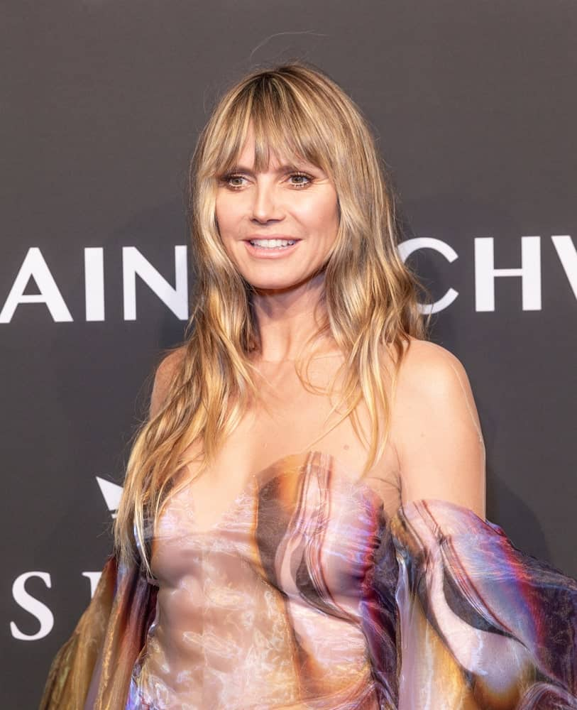 Heidi Klum at Cipriani Wall Street attending an Angel Ball 2019 with a soft wavy hair and bangs. Her honey blonde hair complements the lovely dress she's wearing made by Iris van Herpen.