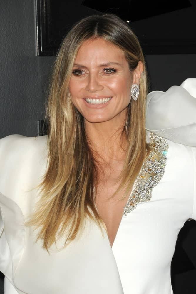 Heidi Klum's eye-catching white dress was balanced by her simple center-parted hairstyle with subtle layers and dark roots. She looked ravishing during the 61st Grammy Awards which she attended on February 10, 2019.