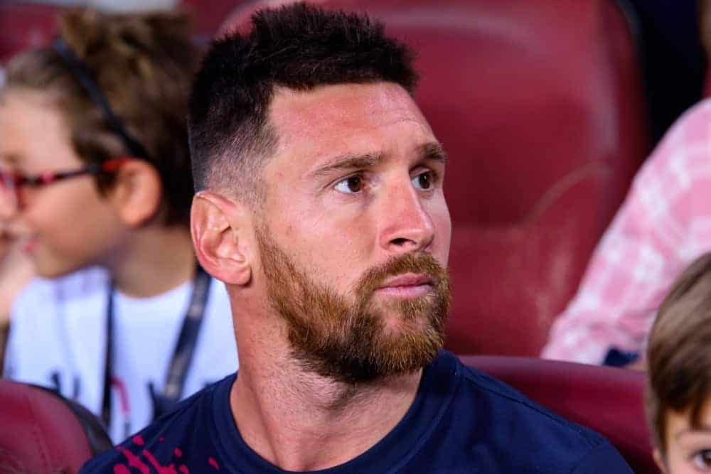 Lionel Messi sat with the spectators at the La Liga match between FC Barcelona and Real Betis at the Camp Nou Stadium on August 25, 2019 in Barcelona, Spain. He wore a sports shirt with his short and spiked fade hairstyle.
