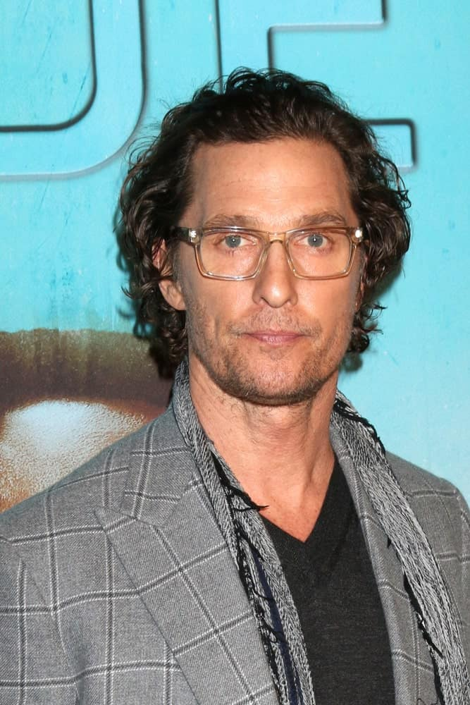 Matthew McConaughey had a messy and dark curly hairstyle with five o'clock shadow at the