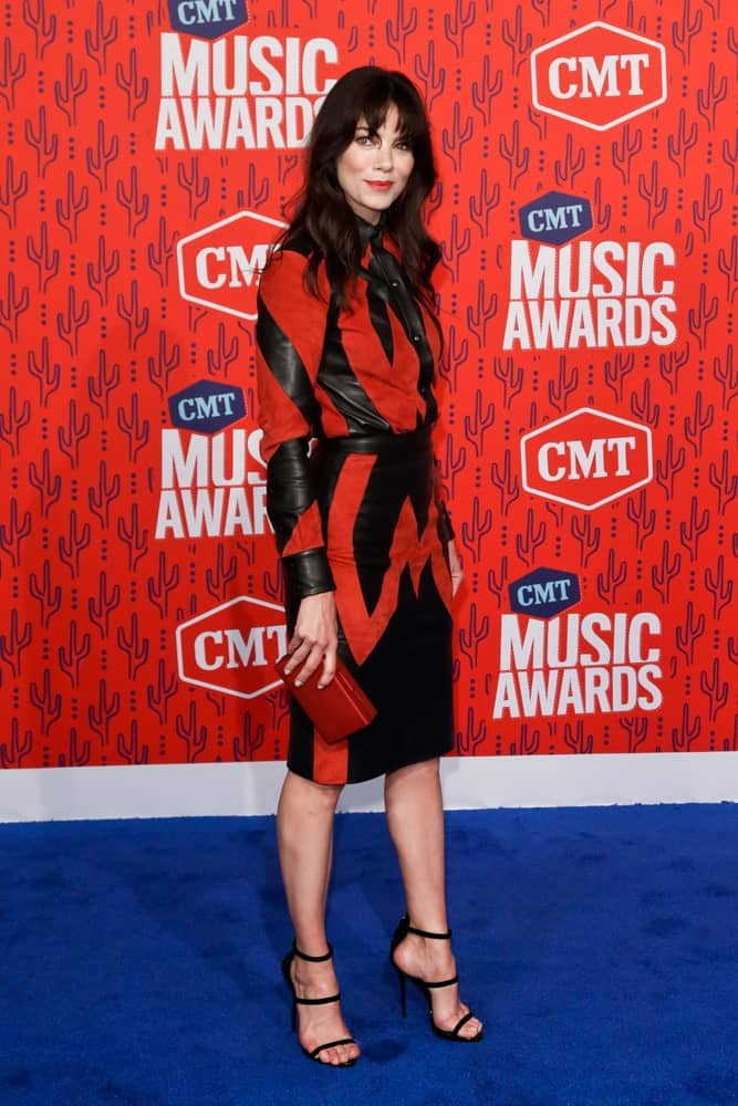 Michelle Monaghan attends the 2019 CMT Music Awards at the Bridgestone Arena on June 5, 2019 in Nashville, Tennessee with a messy relaxed hairstyle with dark curls to match her red and black sexy dress.