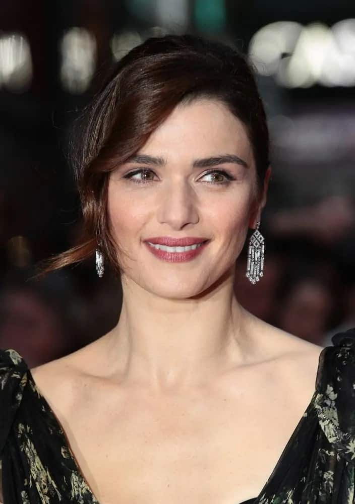 Rachel Weisz wears an elegant black floral gown with her gorgeous brunette locks in a pulled back upstyle with curly side parting as she attends the Lobster premiere on October 12, 2015.