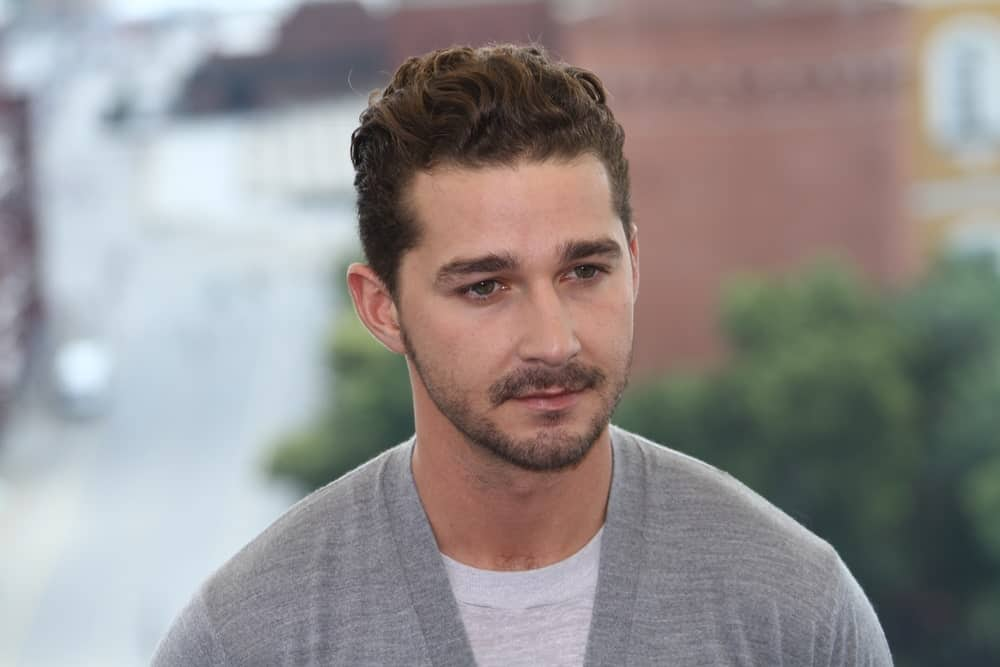 Shia LaBeouf poses for a photocall before global premiere of 'Transformers 3' movie on the roof of the Ritz hotel on June 23, 2011 in Moscow, Russia. He was wearing a simple gray sweatshirt to complement his curly fade hairstyle.