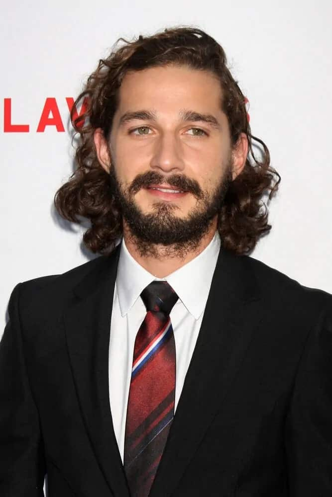 Shia LaBeouf had mid-length dark brown curly hair effortlessly left tousled for a grunge look last August 22, 2012 for the LA premiere of