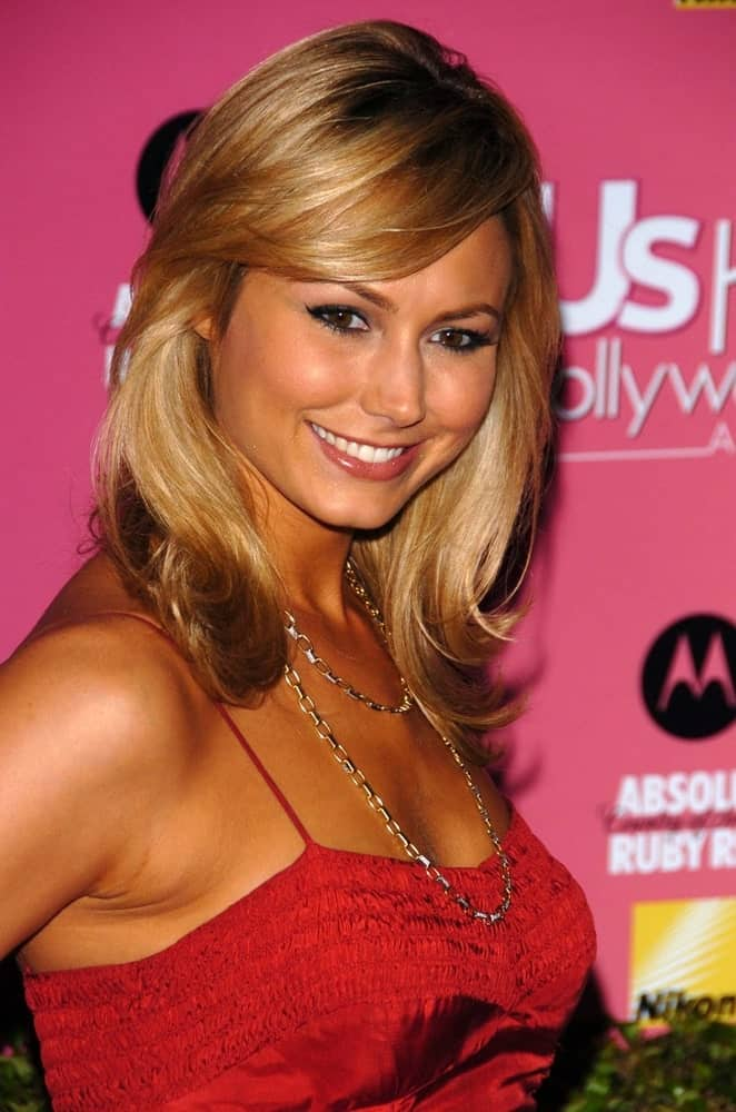 The model flaunts a chic red dress with a layered necklace and a side-swept hair with subtle curls on its ends. This look was worn on April 26, 2006, during the US Weekly Hot Hollywood Awards.