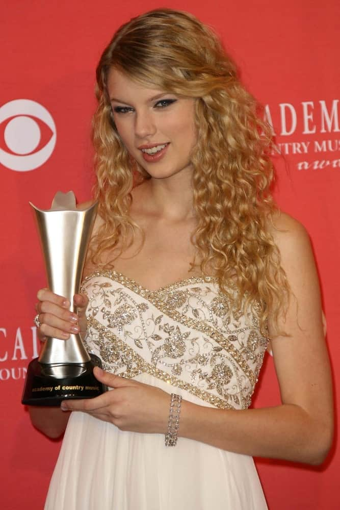 Taylor Swift showed off her curly blonde hair with her bangs pinned to the side during the press room at The 43rd Annual Academy Of Country Music Awards on May 18, 2008.