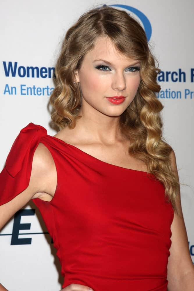 Taylor Swift in a bold red dress complemented with her loose curly hair at the