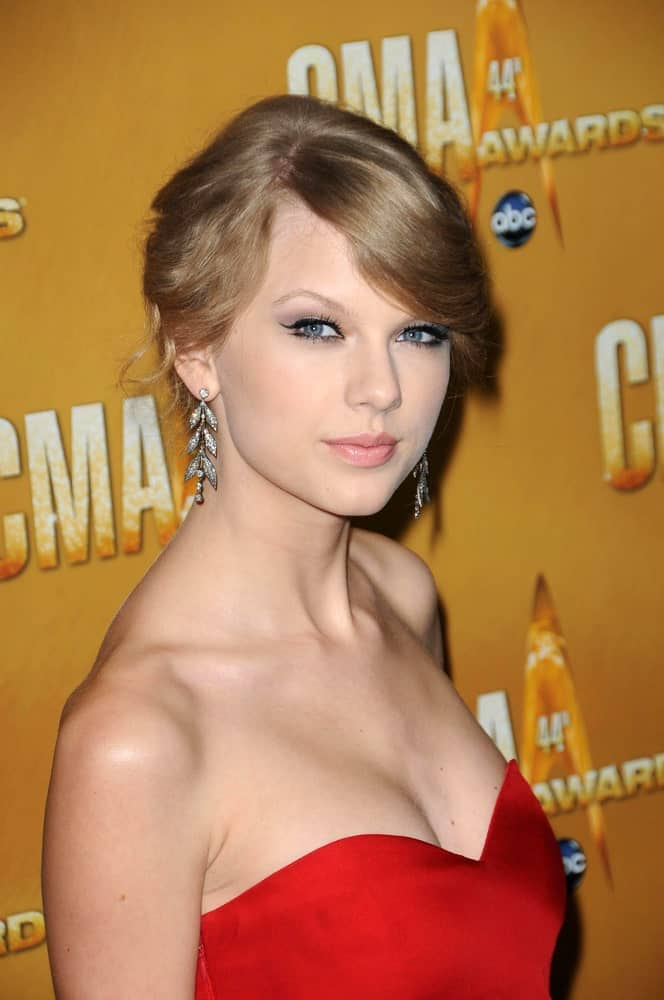 During the 44th Annual CMA Awards at Bridgestone Arena, Nashville, TN on November 10, 2010, Taylor Swift opted for a classic updo with side-swept bangs. She finished the look with a stunning red dress and dangling earrings.