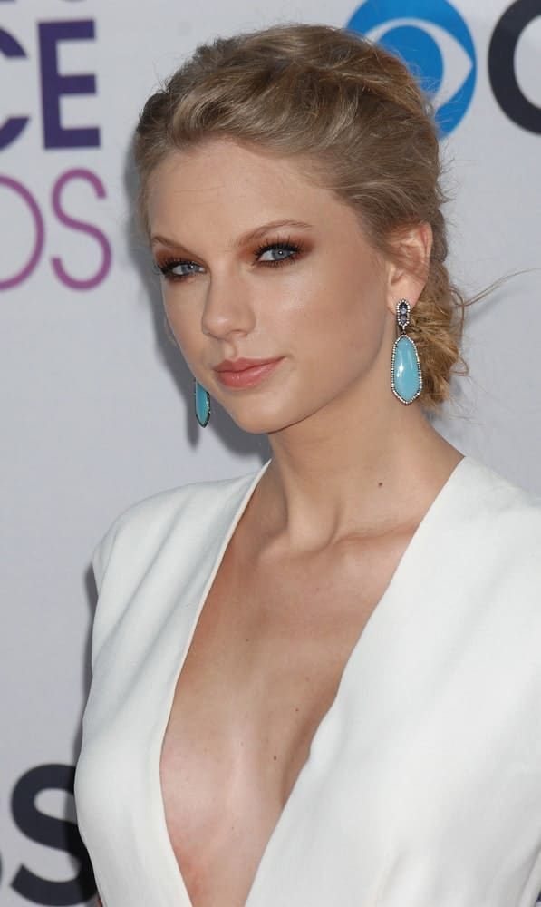 Taylor Swift pinned back her hair in a classic messy updo at the 2013 Peoples Choice Awards on January 9th in Los Angeles, CA. It was completed with a deep V neck outfit and gorgeous blue earrings.