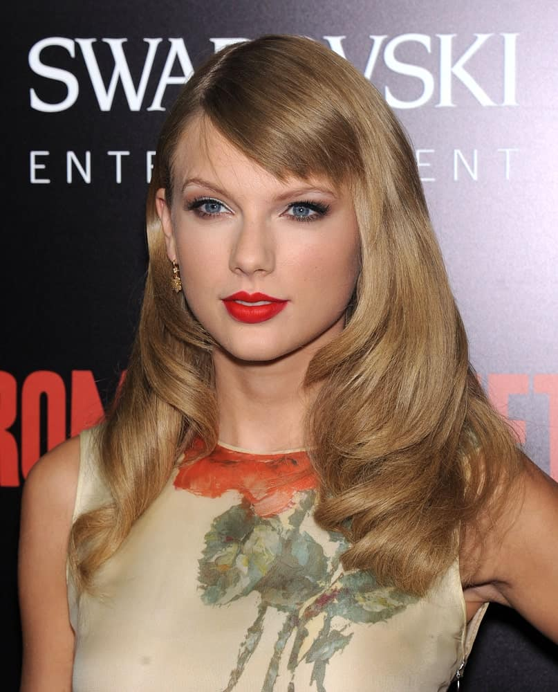 Taylor Swift showed off her straight blonde hair with big curls on the ends along with short side bangs at the