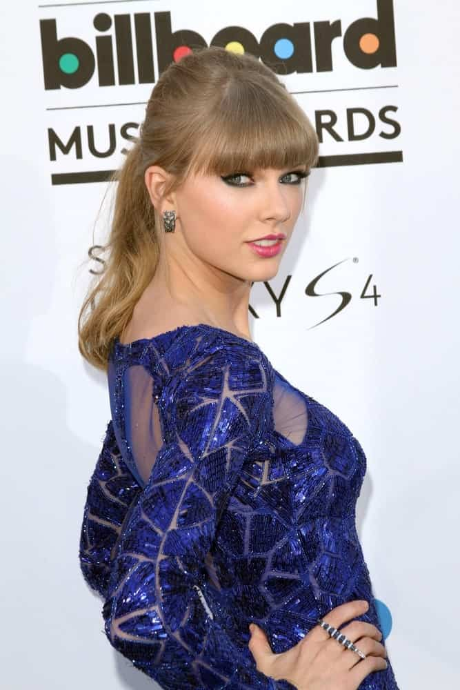 Taylor Swift looking sleek in a blue geometric dress complemented with a high ponytail and blunt bangs at the at the 2013 Billboard Music Awards Arrivals last May 19, 2013.