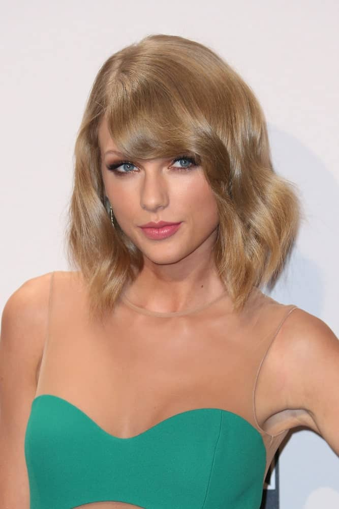 Taylor Swift had a loose wavy hairstyle with side-swept bangs at the 2014 American Music Awards - Press Room at the Nokia Theater on November 23rd.