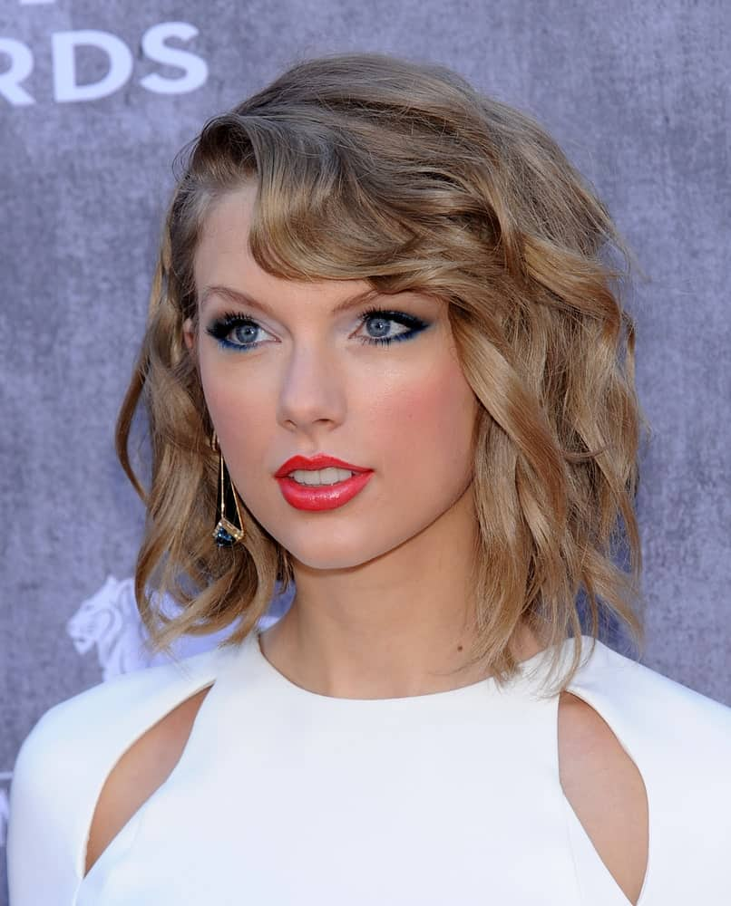 Taylor Swift arrived for the 49th Annual Academy of Country Music Awards on April 06, 2014 with a short wavy hairstyle paired with a trendy white dress.