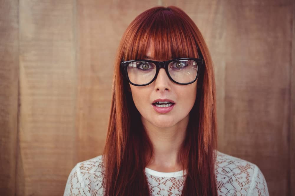 Woman with long straight red hair and blunt bangs (and glasses)
