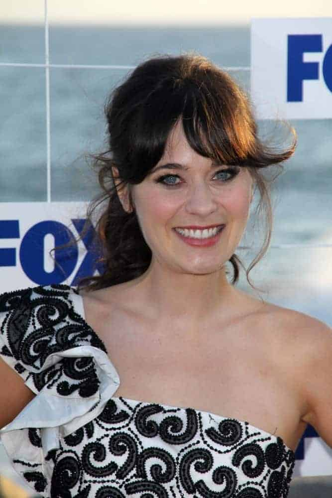 Zooey Deschanel was at the FOX All-Star Party 2011 in Gladstones, Malibu, CA on August 5, 2011. She was seen wearing a black and white dress with a messy ponytail hairstyle that has long bangs.