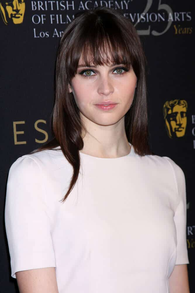 This sleek and straight hair with bangs is a total game changer for Felicity Jones who is a messy upstyle kind of person. This photo was captured at the BAFTA Award Season Tea Party 2012.